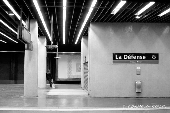 Un homme étrangement seul à la station RER de La Défense attendant son train.